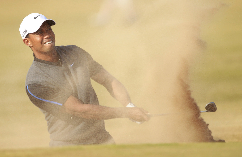 Description of . Tiger Woods of the United States plays out of  a bunker onto the 14th green during the third round of the British Open Golf Championship at Muirfield, Scotland, Saturday July 20, 2013. (AP Photo/Peter Morrison)