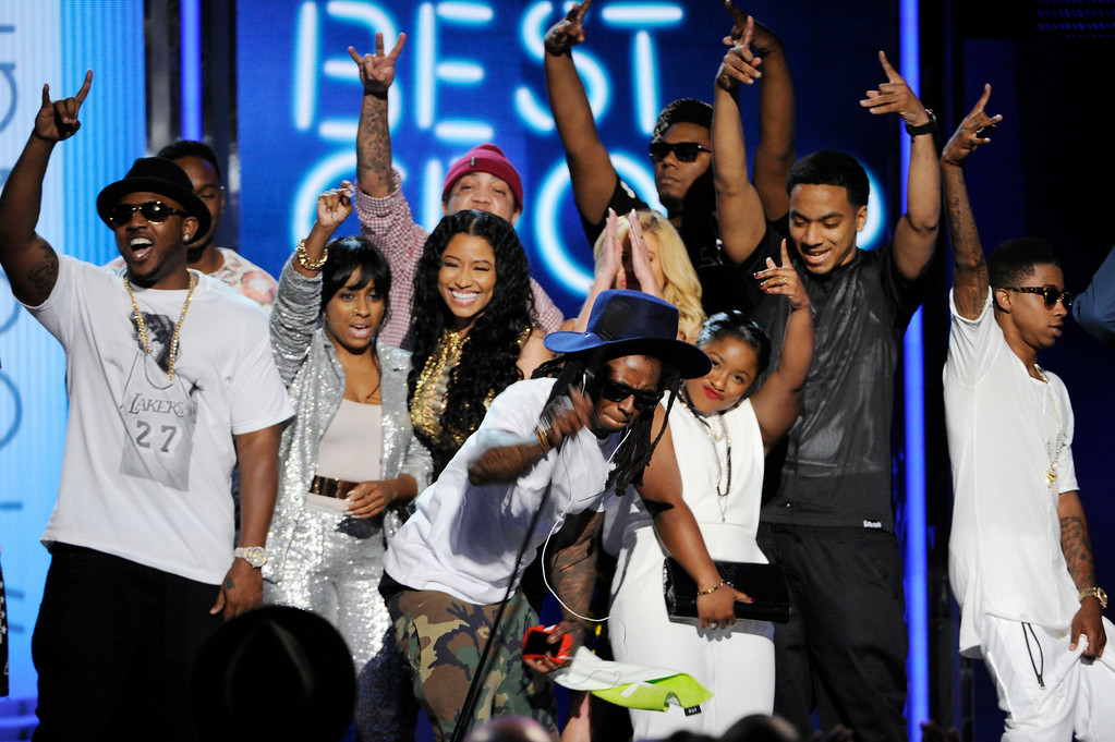Description of . Lil' Wayne, center, slams the microphone onto the ground after Young Money is announced winner of the award for best group at the BET Awards at the Nokia Theatre on Sunday, June 29, 2014, in Los Angeles. (Photo by Chris Pizzello/Invision/AP)