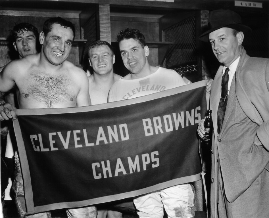 Description of . The Cleveland Browns defeated the Pittsburgh Steelers on at a game in Cleveland, Ohio, Dec. 12, 1954, to win the NFL divisional championship. Coach Paul Brown, right, poses with some of the players in the dressing room after the game. From left to right they are Pete Brewster, Lou Groza, Chuck Noll, and Otto Graham. (AP Photo/Julian C. Wilson)