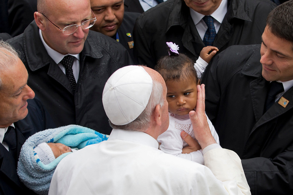 Description of . Pope Francis kisses a baby girl as he is surrounded by security during his visit to the Varginha slum in Rio de Janeiro, Brazil, Thursday, July 25, 2013. Francis on Thursday visited one of Rio de Janeiro's shantytowns, or favelas, a place that saw such rough violence in the past that it's known by locals as the Gaza Strip.  (AP Photo/Victor R. Caivano)