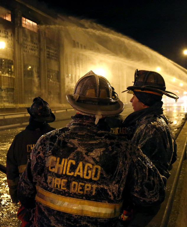 Description of . Chicago firefighters are covered in ice from single digit temperatures as they take a break from a five-alarm blaze in a warehouse on the city's South Side, Bridgeport neighborhood Wednesday, Jan. 23, 2013, in Chicago. (AP Photo/Charles Rex Arbogast)