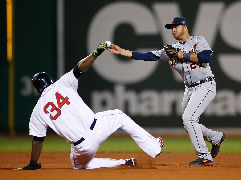 Description of . Detroit Tigers shortstop Jhonny Peralta (27) throws out Boston Red Sox left fielder Mike Carp at first base to turn a double play in the fourth inning taking Boston Red Sox's David Ortiz (34) out at second base during Game 2 of the American League baseball championship series Sunday, Oct. 13, 2013, in Boston. (AP Photo/Elise Amendola)