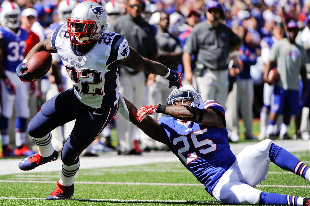 Description of . New England Patriots' Stevan Ridley (22) breaks a tackle by Buffalo Bills' Da'Norris Searcy (25) during the first half of an NFL football game on Sunday, Sept. 8, 2013, in Orchard Park. (AP Photo/Gary Wiepert)
