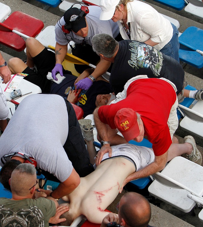 Description of . Injured spectators are treated after a crash at the conclusion of the NASCAR Nationwide Series auto race Saturday, Feb. 23, 2013, at Daytona International Speedway in Daytona Beach, Fla. Driver Kyle Larson's car hit the safety fence sending car parts and other debris flying into the stands. (AP Photo/David Graham)