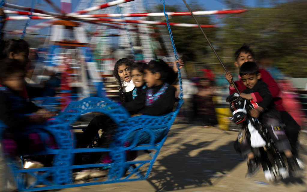 Description of . Pakistani Christian children celebrate Christmas on a ride in Islamabad's slums, Pakistan. Wednesday, Dec. 25, 2013. Christians are a minority in Pakistan and constitute about 1.6% of the country's population. (AP Photo/B.K. Bangash)