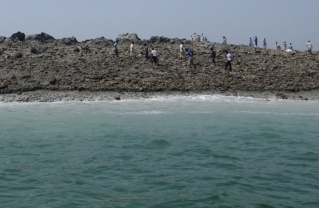 Description of . In this photo released by the Pakistani Government, Pakistani men walk on an island that appeared 2 kilometers off the coastline of Gwadar on September 25, 2013, after an earthquake the day before. The National Institute of Oceanography has sent a team to survey the island, which stands about 20 metres (70 feet) high. Pakistani rescuers strived to reach victims of a huge earthquake that killed more than 230 people and toppled thousands of mud-built homes when it hit the country's southwest with enough force to create a new island off the coast. AFP PHOTO/ Pakistan Government