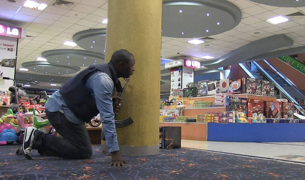 Description of . An image grab taken from AFP TV shows an armed policeman taking position inside a shopping mall following an attack by masked gunmen in Nairobi on September 21, 2013.  AFP PHOTO/AFPTV/NICHOLE Sobecki/AFP/Getty Images