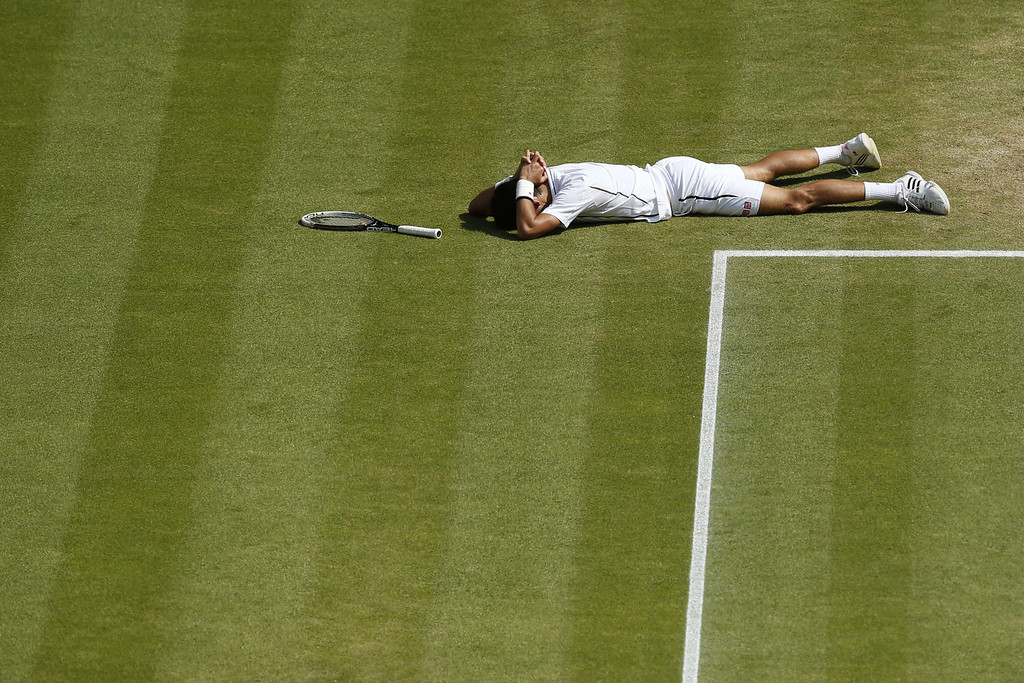 Description of . Serbia\'s Novak Djokovic lies on the floor after diving  to return against Argentina\'s Juan Martin Del Potro during their men\'s singles semi-final match on day eleven of the 2013 Wimbledon Championships tennis tournament at the All England Club in Wimbledon, southwest London, on July 5, 2013. JONATHAN BRADY/AFP/Getty Images