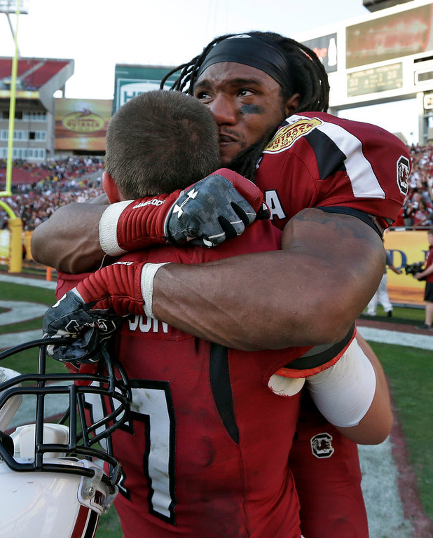 Description of . South Carolina running back Kenny Miles (31) celebrates with quarterback Dylan Thompson (17) after they defeated Michigan 33-28 in the Outback Bowl NCAA college football game, Tuesday, Jan. 1, 2013, in Tampa, Fla.  (AP Photo/Chris O'Meara)