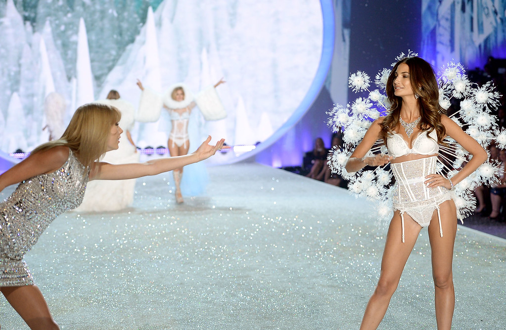 Description of . Singer Taylor Swift (L) performs and model Lily Aldridge walks the runway at the 2013 Victoria's Secret Fashion Show at Lexington Avenue Armory on November 13, 2013 in New York City.  (Photo by Dimitrios Kambouris/Getty Images for Victoria's Secret)