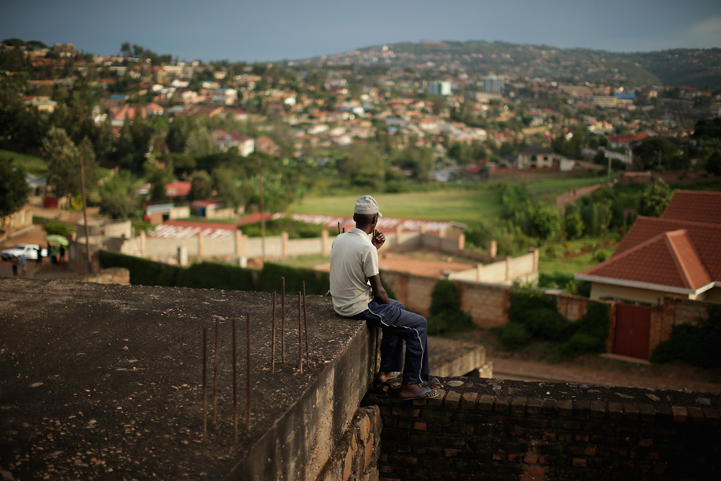 . A man sits as the evening sun falls over the Kicukiro District of the capital April 5, 2014 in Kigali, Rwanda. Built in hilly country in the heart of the African continent, Kigali sprawls across four ridges and the valleys in between. Rwanda is preparing to commemorate the 20th anniversary of the country\'s 1994 genocide, when more than 800,000 ethnic Tutsi and moderate Hutus were slaughtered over a 100 day period.  (Photo by Chip Somodevilla/Getty Images)