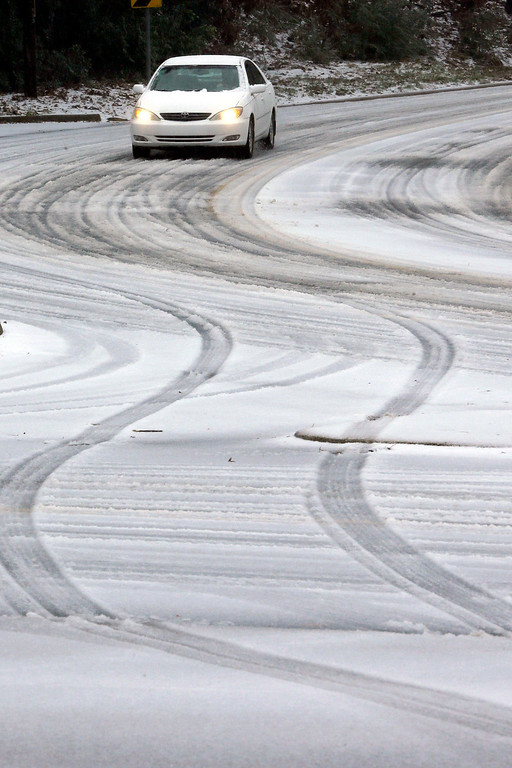 Description of . A car makes its way down a sleet-covered hill in Little Rock, Ark., Friday, Dec. 6, 2013. Weather forecasters lifted an ice storm warning Friday for much of central Arkansas. (AP Photo/Danny Johnston)