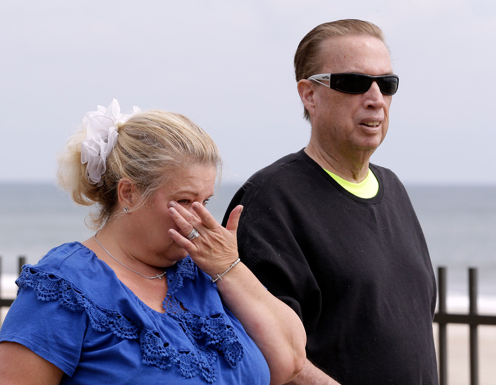Description of . Julie Migliorisi, left, of Seaside Heights, N.J., wipes tears off her face while walking with her husband Richard Migliorisi moments after the couple met with New Jersey Gov. Chris Christie, who visited the area hit by a massive fire a day earlier, Friday, Sept. 13, 2013, in Seaside Park, N.J. The fire, which apparently started in an ice cream shop and spread several blocks, hit the recently repaired boardwalk, which was damaged last year by Superstorm Sandy. There were no reports of any injuries. The Migliorisis were displaced from their home when Sandy ripped through the region and have been living in Bergen County while their home is repaired. (AP Photo/Julio Cortez)