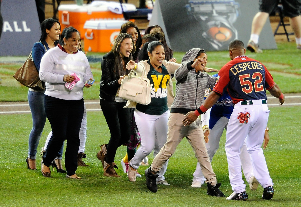 Description of . American League All-Star Yoenis Cespedes #52 of the Oakland A's celebrates with his family after winning the Gillette Home Run Derby at Target Field on July 14, 2014 in Minneapolis, Minnesota.  (Photo by Hannah Foslien/Getty Images)