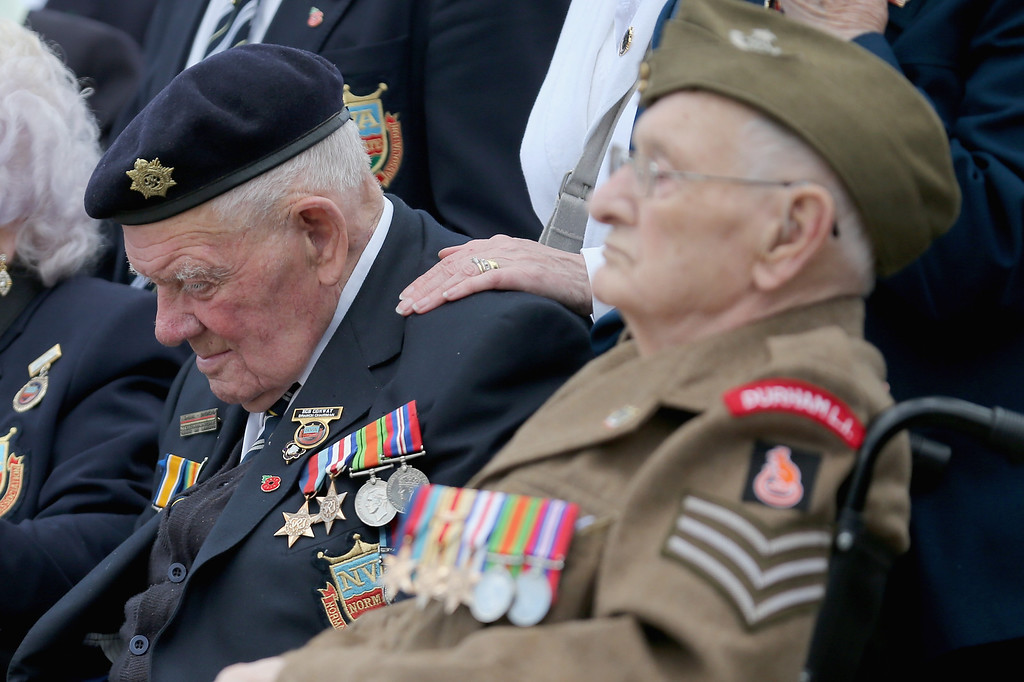 Description of . D-Day veterans Ken Scott, aged 98, and Bob Conway 88 (L), pause for thought during the Royal Artillery Commemoration Parade and service on June 5, 2014 in Hermanville, France. (Photo by Christopher Furlong/Getty Images)