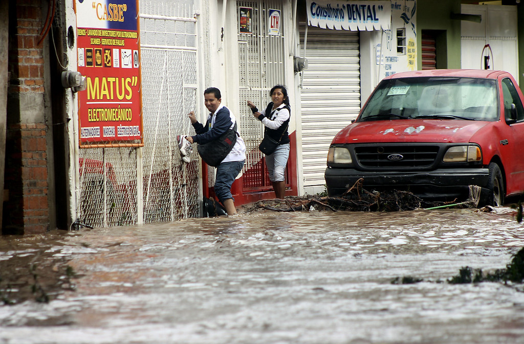 Description of . Residents attemp to cross a flooded street in Chilpancingo, state of Guerrero, Mexico, on September 17, 2013. Mexican authorities scrambled Tuesday to launch an air lift to evacuate tens of thousands of tourists stranded amid floods in the resort of Acapulco following a pair of deadly storms. The official death toll rose to 47 after the tropical storms, Ingrid and Manuel, swarmed large swaths of the country during a three-day holiday weekend, sparking landslides and causing rivers to overflow in several states.  EDUARDO GUERRERO/AFP/Getty Images