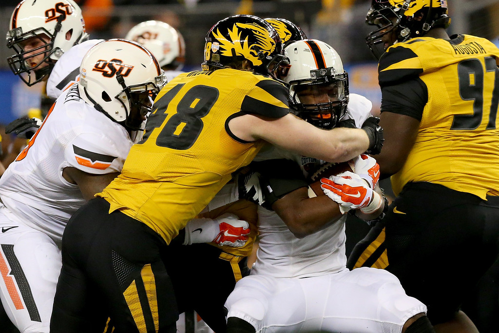 Description of . ARLINGTON, TX - JANUARY 03:  Running back Desmond Roland #26 of the Oklahoma State Cowboys is tackled by Andrew Wilson #48 of the Missouri Tigers in the first quarter during the AT&T Cotton Bowl on January 3, 2014 in Arlington, Texas.  (Photo by Ronald Martinez/Getty Images)