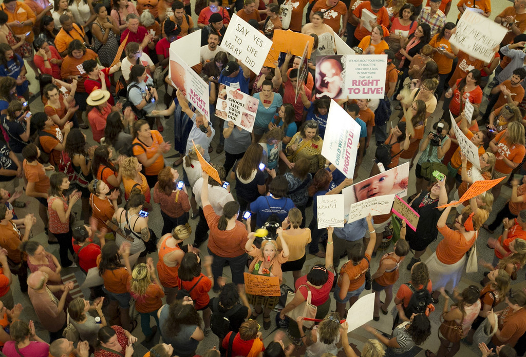 Description of . People on both sides of the abortion debate gather during the Senate's debate on Friday July 12, 2013, in the Capitol in Austin, Texas. Texas Republicans on Friday defended a sweeping abortion proposal against Democratic attempts to show the tough restrictions were not only unnecessary, but also unconstitutional. (AP Photo/Austin American-Statesman, Jay Janner)