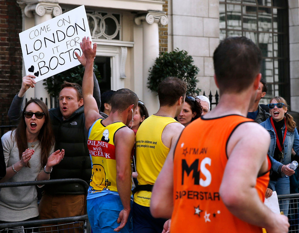Description of . Spectators hold a placard in support of Boston as runners pass during the London Marathon in central London April 21, 2013. Undaunted by the Boston Marathon bombings, big crowds lined the route of London 's mass road race on Sunday to cheer on around 36,000 runners, many of whom wore black ribbons to remember the dead and wounded. REUTERS/Eddie Keogh