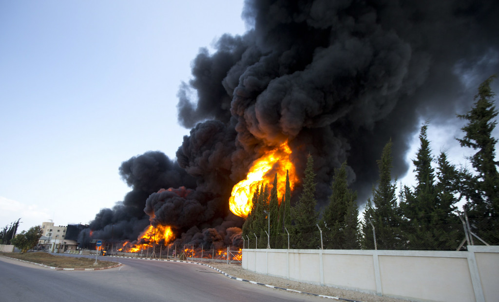 Description of . Flames engulf the fuel tanks of the only power plant supplying electricity to the Gaza Strip after it was hit by overnight Israeli shelling, on July 29, 2014, in the south of Gaza City.  AFP PHOTO/MAHMUD HAMS/AFP/Getty Images