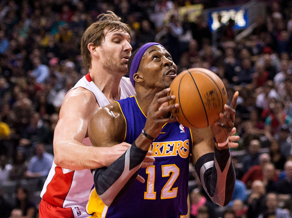 Description of . Los Angeles Lakers forward Dwight Howard, right, drives past Aaron Gray, left, during first half NBA basketball action in Toronto on Sunday Jan. 20, 2013. (AP Photo/THE CANADIAN PRESS,Nathan Denette)