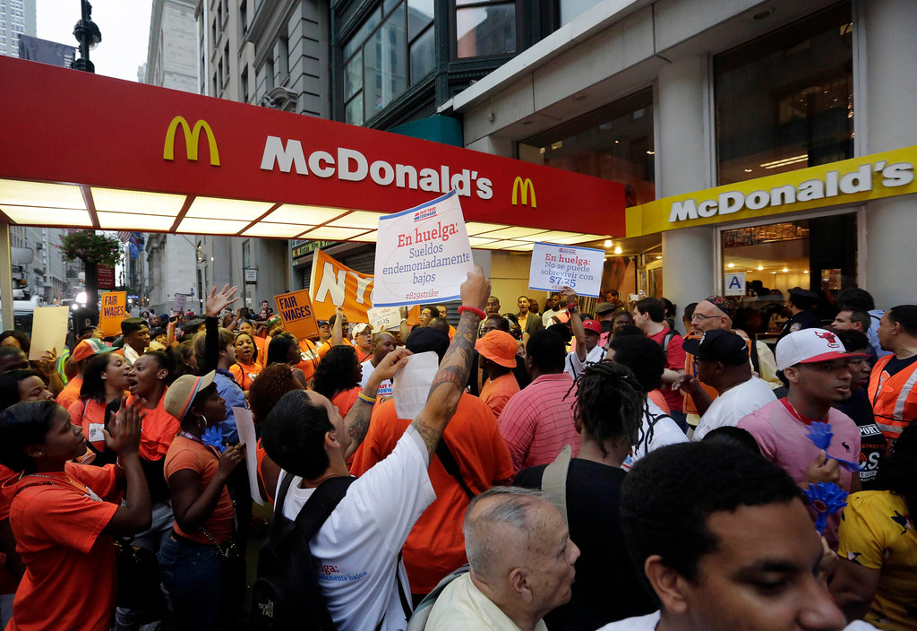 Description of . Protesting fast food workers demonstrate outside a McDonald's restaurant on New York's Fifth Avenue, Thursday, Aug. 29, 2013. Organizers say thousands of fast-food workers are set to stage walkouts in dozens of cities around the country Thursday, part of a push to get chains such as McDonald's, Taco Bell and Wendy's to pay workers higher wages. (AP Photo/Richard Drew)