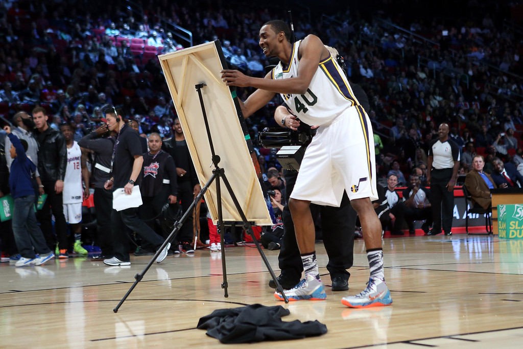 Description of . HOUSTON, TX - FEBRUARY 16:  Jeremy Evans of the Utah Jazz signs a painting of himself after he dunked over it in the final round during the Sprite Slam Dunk Contest part of 2013 NBA All-Star Weekend at the Toyota Center on February 16, 2013 in Houston, Texas.  (Photo by Ronald Martinez/Getty Images)