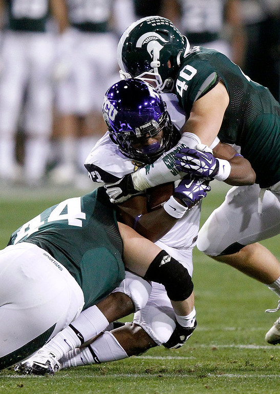 Description of . TCU running back B.J. Catalon, center, is tackled between Michigan State defensive end Marcus Rush, left, and linebacker Max Bullough, right, during the first half of the Buffalo Wild Wings Bowl NCAA college football game, Saturday, Dec. 29, 2012, in Tempe, Ariz. (AP Photo/Paul Connors)