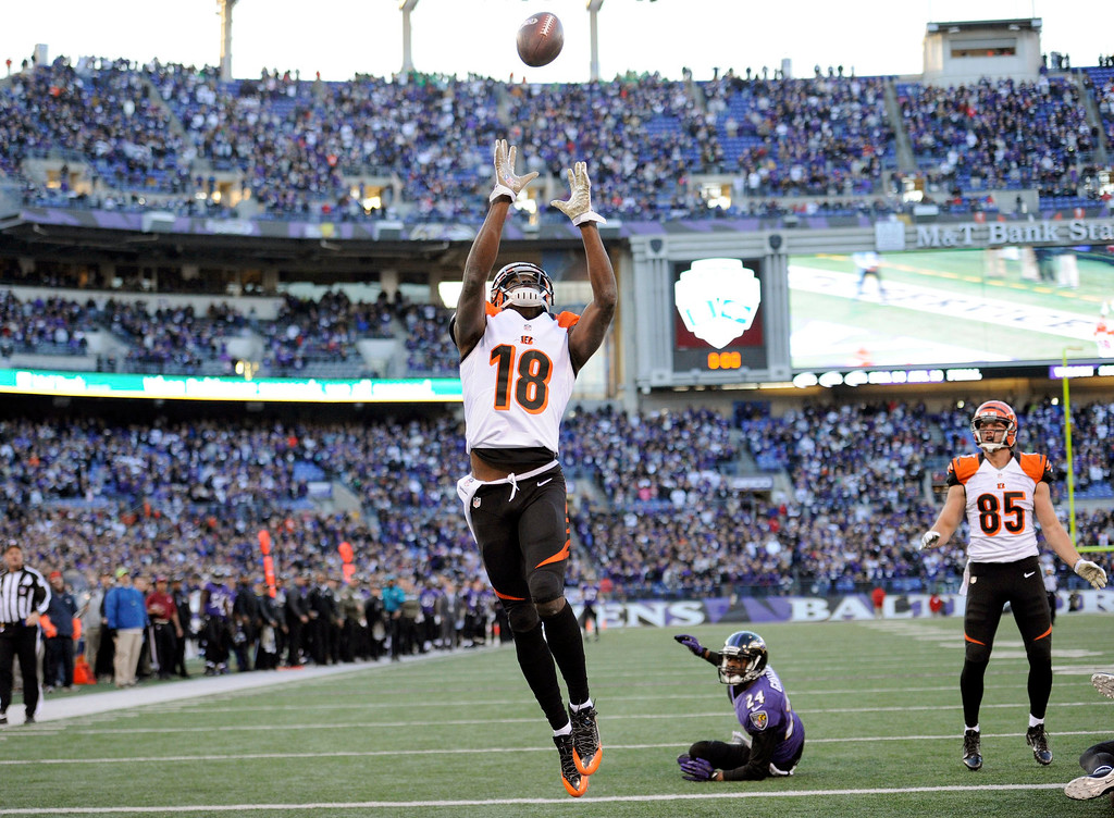 Description of . Cincinnati Bengals wide receiver A.J. Green reaches for a bobbled ball for a touchdown to tie the game as Baltimore Ravens cornerback Corey Graham looks during the second half of a NFL football game against the Baltimore Ravens in Baltimore, Sunday, Nov. 10, 2013. (AP Photo/Nick Wass)