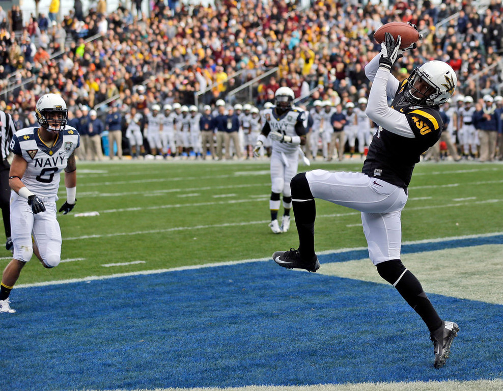 Description of . Arizona State wide receiver Alonzo Agwuenu, right, catches an 11-yard touchdown pass near Navy safety Wave Ryder (8) during the first half of the Fight Hunger Bowl NCAA college football game in San Francisco, Saturday, Dec. 29, 2012. (AP Photo/Marcio Jose Sanchez)