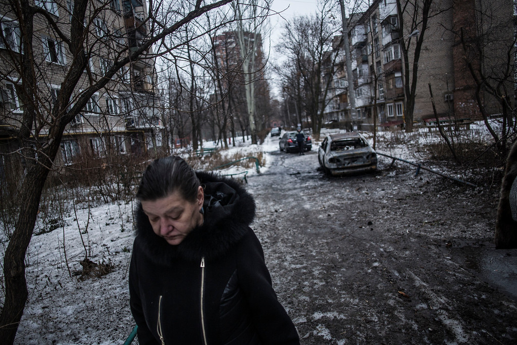 Description of . A woman walks through a residential area hit by the Ukrainian Army Artillery in Voroshilovsky area, center of Donetsk, Ukraine. Sunday, Jan. 18, 2015. The separatist stronghold, Donetsk, was shaken by intense outgoing and incoming artillery fire as a bitter battle raged for control over the city's airport. Streets in the city, which was home to 1 million people before unrest erupted in spring, were completely deserted and the windows of apartments in the center rattled from incessant rocket and mortar fire. (AP Photo/Manu Brabo)