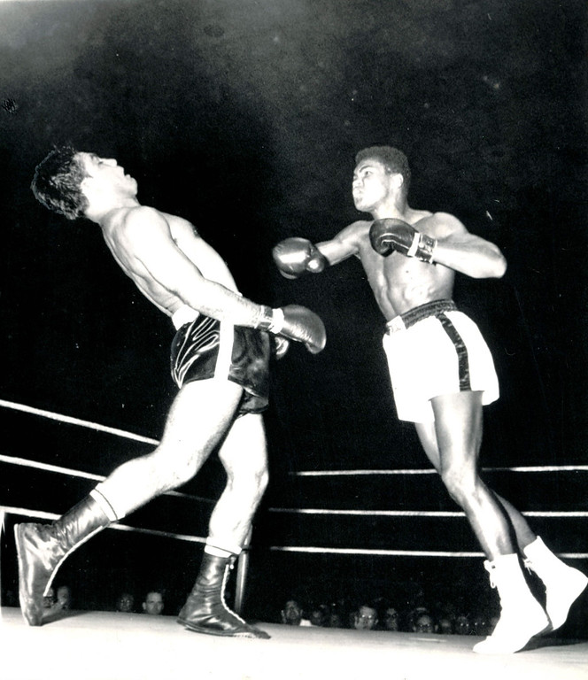 Description of . Rock 'n' Roll in the Ring   Alex Miteff stiffens shortly before hitting the canvas under furious attack by Cassius Clay.  The Argentinian signaled the referee he was unable to continue their nationally televised Louisville, Ky., fight and Clay was awarded a sixth-round technical knockout. 1961  Credit: AP