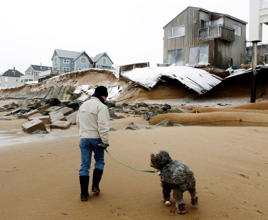 . John March walks his dog Grommit past damaged houses along the beach in Plum Island in Newbury, Mass., Saturday, Feb. 9, 2013. (AP Photo/Winslow Townson)