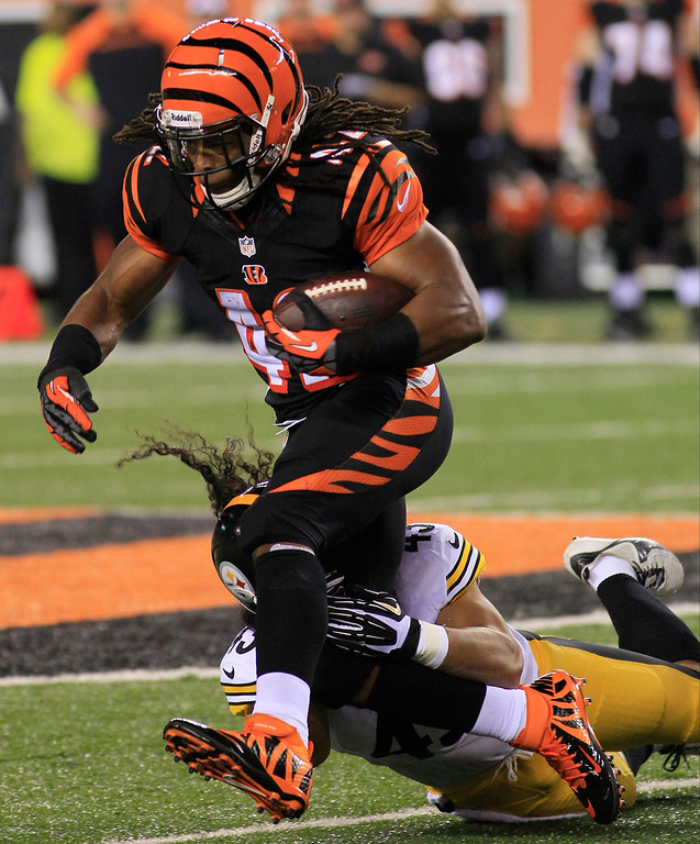 Description of . Cincinnati Bengals running back BenJarvus Green-Ellis (42) is tackled by Pittsburgh Steelers strong safety Troy Polamalu in the first half of an NFL football game, Monday, Sept. 16, 2013, in Cincinnati. (AP Photo/Tom Uhlman)
