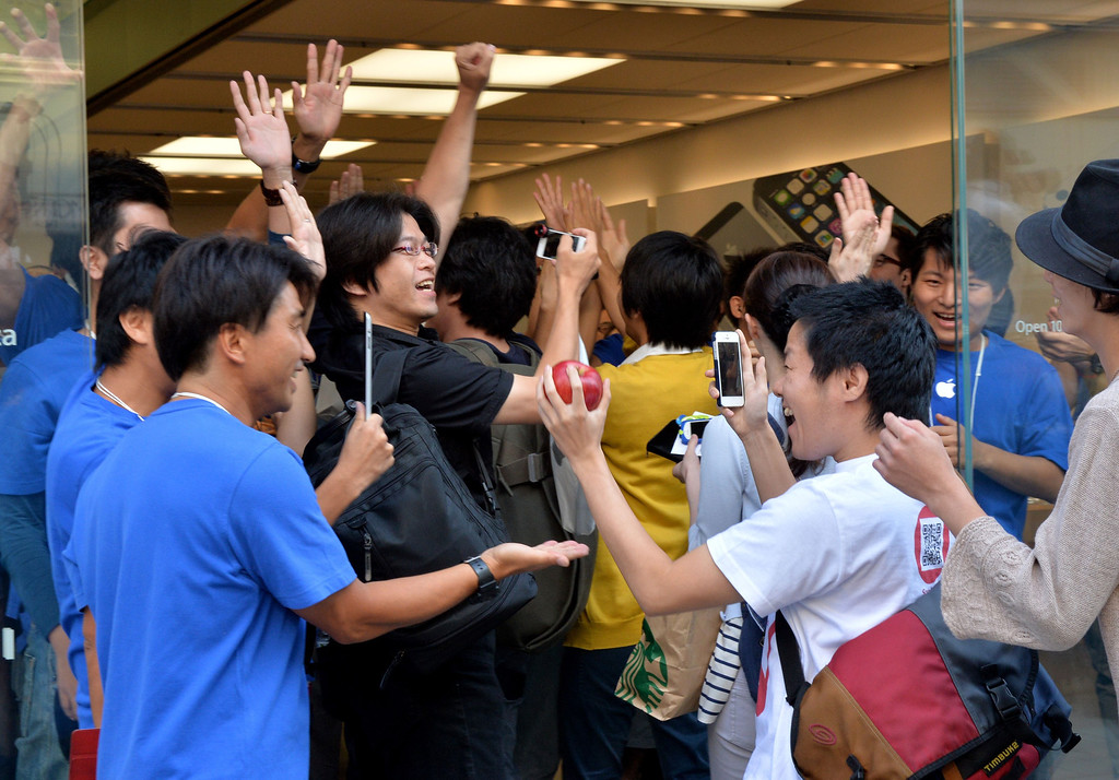 Description of . Apple Store employees greet their first customers after 700 Apple fans queued to buy Apple's new iPhone 5s and 5c smartphones at the Apple Store in Tokyo on September 20, 2013. Apple acolytes got their hands on new iPhones in the global roll-out of two new models, but failure to make headway in China and complaints about the price struck a sour note. AFP PHOTO / Yoshikazu TSUNOYOSHIKAZU TSUNO/AFP/Getty Images