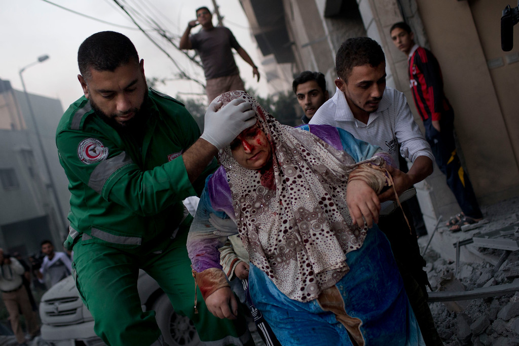 Description of . In this Nov. 19, 2012 photo, a Palestinian woman is helped after being injured during an Israeli forces strike on a soccer field next to her house in Gaza City. This photo was one in a series of images by Associated Press photographer Bernat Armangue that won the first place prize in the World Press Photo 2013 photo contest for the Spot News series category.  (AP Photo/Bernat Armangue, File)