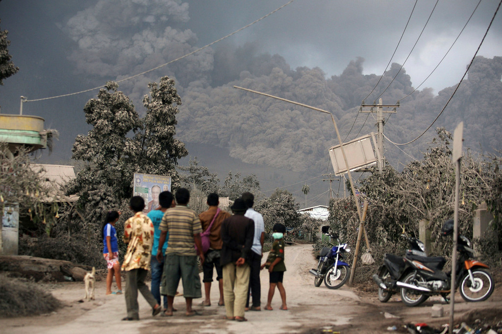 Description of . Villagers watch as Mount Sinabung releases pyroclastic flow in Sibintun, North Sumatra, Indonesia, Monday, Jan. 6, 2014. The volcano unleashed more clouds of searing gas avalanching down the mountain with a thunderous roar, forcing tens of thousands of people packed emergency shelters. (AP Photo/Binsar Bakkara)