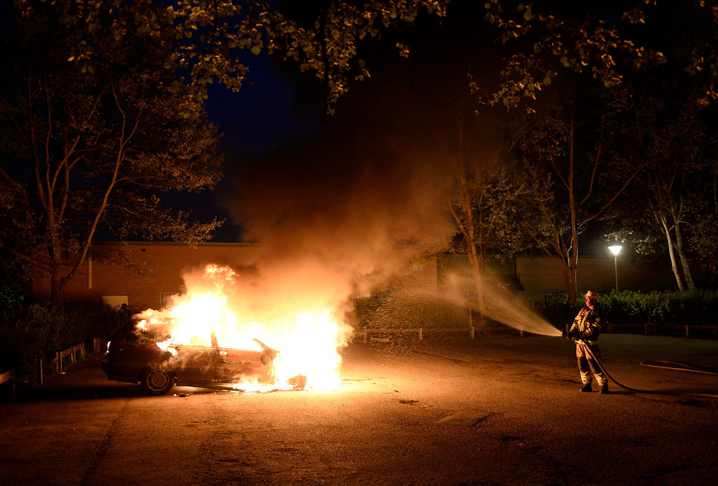 Description of . Firemen extinguish a burning car in Kista after youths rioted in few differant suburbs around Stockholm on May 21, 2013. Youths in the immigrant-heavy Stockholm suburb of Husby torched cars and threw rocks at police, in riots believed to be linked to the deadly police shooting of a local resident.  JONATHAN NACKSTRAND/AFP/Getty Images