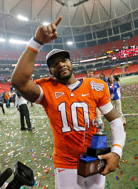 . Clemson quarterback Tajh Boyd walks off he field with the MVP trophy after the Chick-fil-A Bowl NCAA college football game against LSU, Monday, Dec. 31, 2012, in Atlanta. Clemson won 25-24. (AP Photo/John Bazemore)