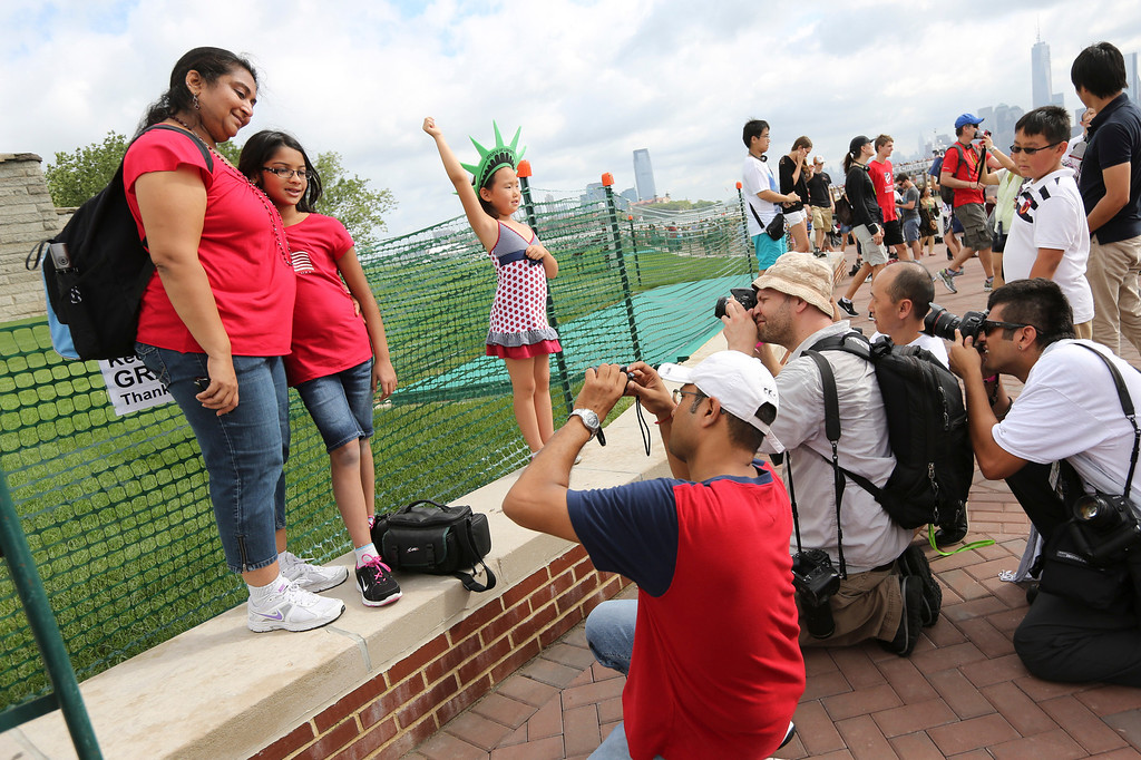 Description of . Photographers take photos of people posing for pictures a the base of the Statue of Liberty, Thursday, July 4, 2013, in New York. The Statue of Liberty finally reopened on the Fourth of July months after Superstorm Sandy swamped Liberty Island in New York Harbor as Americans across the country marked the holiday with fireworks and barbecues. (AP Photo/Mary Altaffer)
