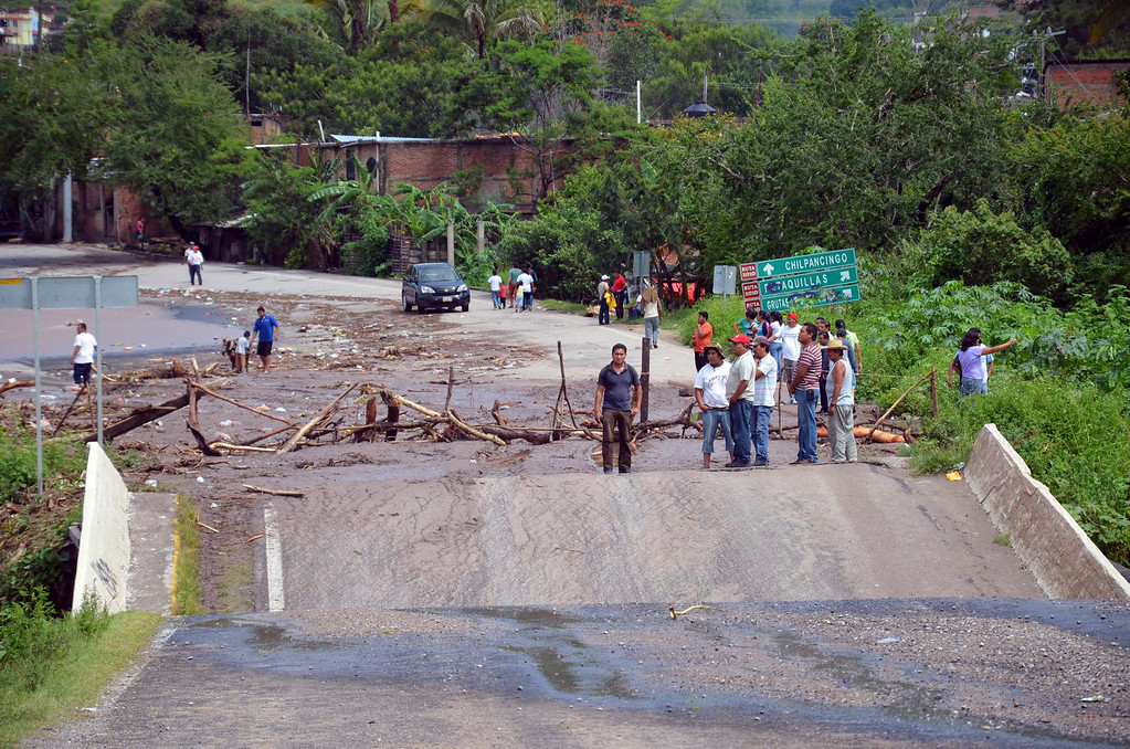 Description of . People stand next to a collapsed bridge over the Huacapa River near the town of Petaquillas, Mexico, Tuesday, Sept. 17, 2013. Twin storms left scenes of havoc on both of Mexico's coasts on Tuesday, with tens of thousands of tourists stranded in resort city of Acapulco on the Pacific and heavy damage reported along the Gulf coast. (AP Photo/Alejandrino Gonzalez)