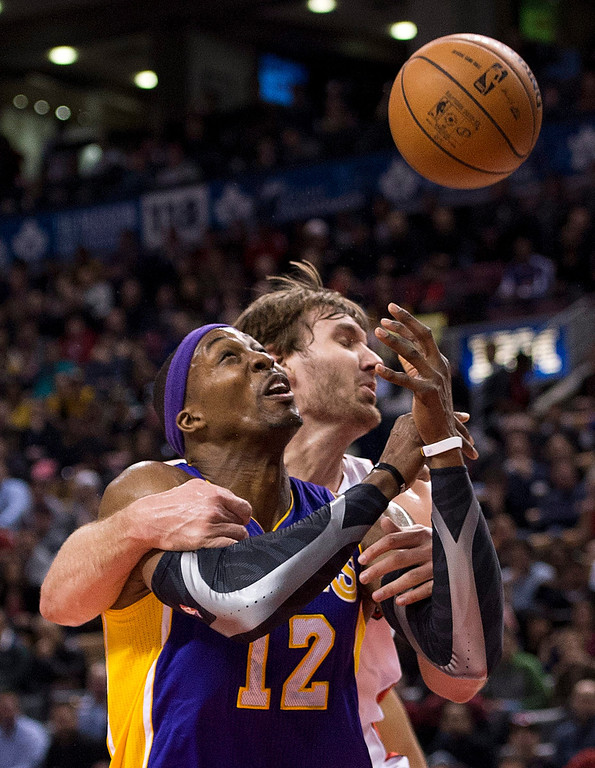 Description of . Los Angeles Lakers forward Dwight Howard, left, drives past Aaron Gray, right, during first half NBA basketball action in Toronto on Sunday Jan. 20, 2013. (AP Photo/THE CANADIAN PRESS,Nathan Denette)