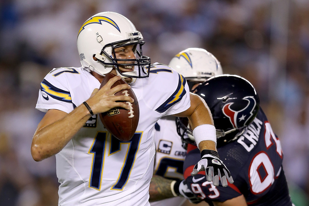Description of . Quarterback Philip Rivers #17 of the San Diego Chargers looks to avoid the rush by defensive end Jared Crick #93 of the Houston Texans in the first quarter at Qualcomm Stadium on September 9, 2013 in San Diego, California.  (Photo by Jeff Gross/Getty Images)