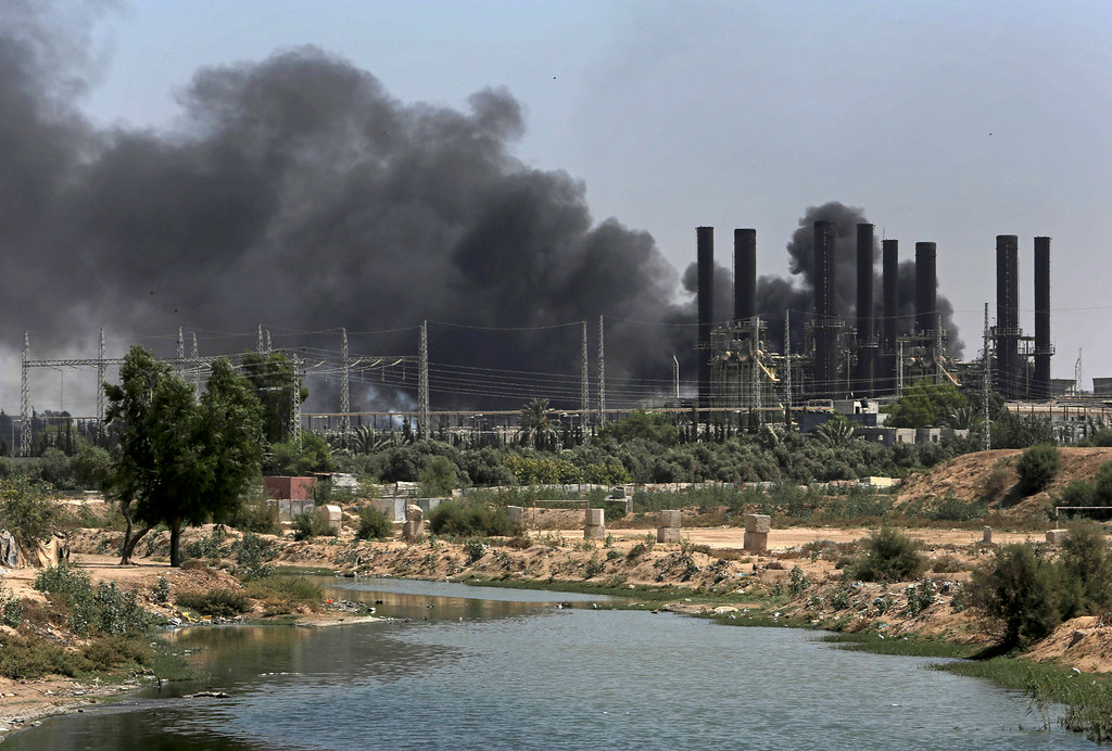 Description of . Smoke billows from Gaza's power plant after it was hit by Israeli strikes in the Nusseirat Refugee Camp, central Gaza Strip,Tuesday, July 29, 2014.  Israel escalated its military campaign against Hamas on Tuesday, striking symbols of the group's control in Gaza and firing tank shells that shut down the strip's only power plant in the heaviest bombardment in the fighting so far.  (AP Photo/Adel Hana)