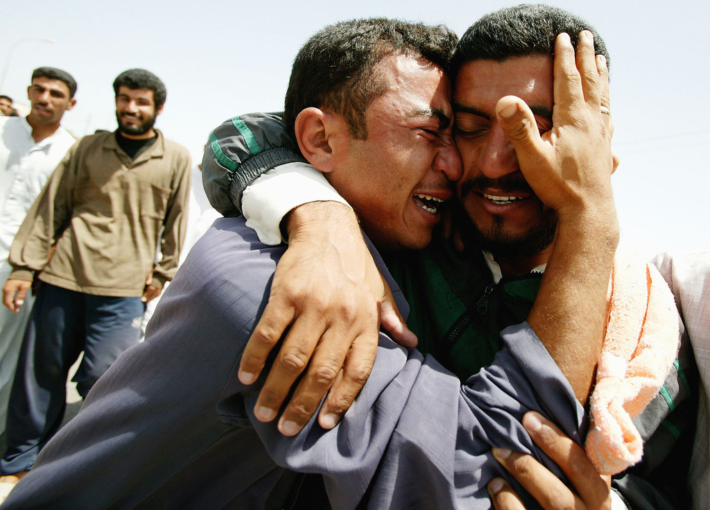 Description of . Two men, who are overcome with emotion after being released from Abu Ghraib prison, hug May 14, 2004 in the city of Baquba, outside of Baghdad, Iraq. One hundred and eight-three prisoners were released from Abu Ghraib prison on May 14 after they were driven up through Tikrit and finally released in Baquba. (Photo by Brent Stirton/Getty Images)