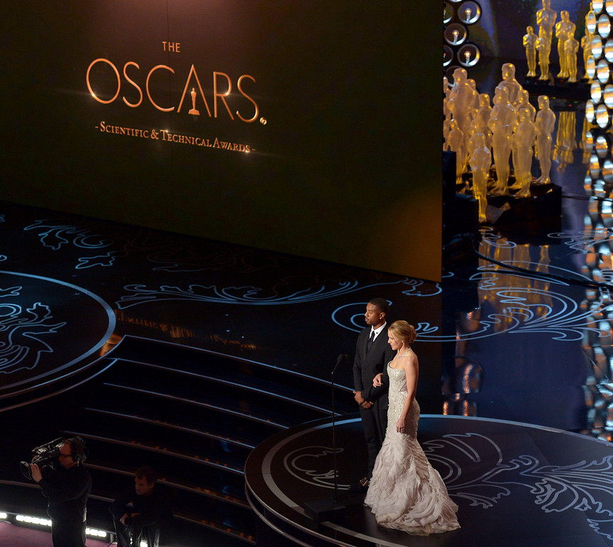 Description of . Michael B. Jordan, left, and Kristen Bell speak on stage during the Oscars at the Dolby Theatre on Sunday, March 2, 2014, in Los Angeles.  (Photo by John Shearer/Invision/AP)