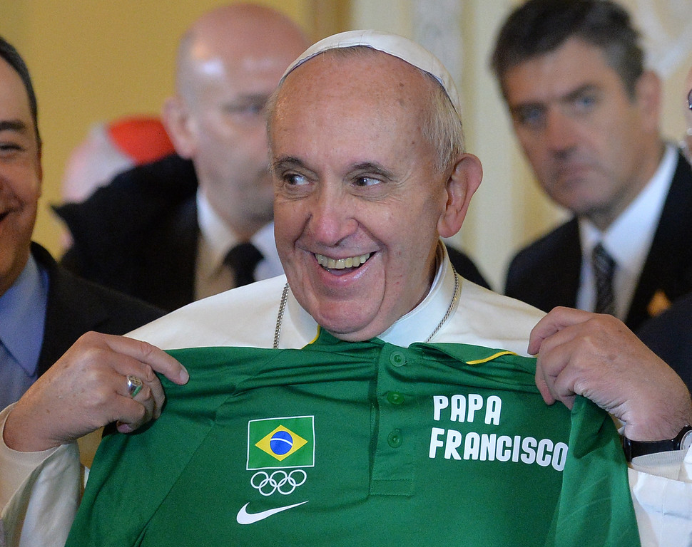 Description of . Pope Francis holds up an Olympic T-shirt with his name on it given to him in Rio de Janeiro, Brazil, Thursday, July 25, 2013.  Francis blessed the Olympic flag, visited a slum and will address young Roman Catholics in Rio de Janeiro's Copacabana beach on Thursday, as Latin America's first pope continued his inaugural international trip as pontiff. The shirt was given to him by Carlos Arthur Nuzman, president of the Brazilian Olympic Committee. (AP Photo/Luca Zennaro, Pool)