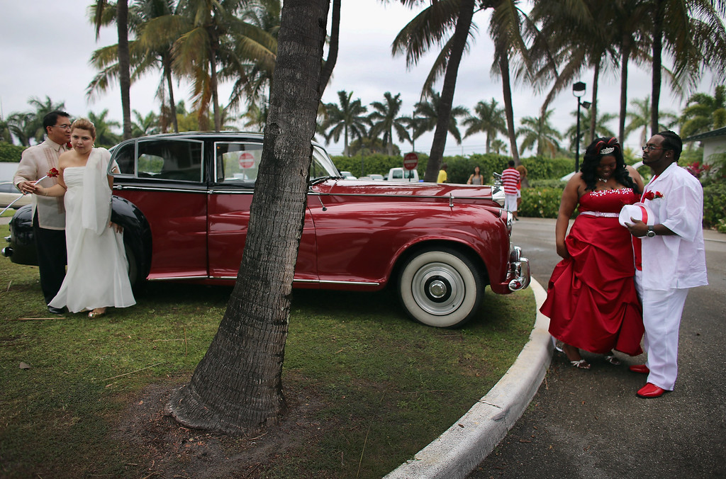. Newlyweds  Rem David (L) and Jenny Briceno (2nd L) and Karean Butler (2nd R) and Karlo Butler walk near a Rolls-Royce after taking part in a group Valentine\'s day wedding at the National Croquet Center on February 14, 2013 in West Palm Beach, Florida. The group wedding ceremony is put on by the Palm Beach Country Clerk & Comptroller\'s office and approximately 40 couples to tied the knot.  (Photo by Joe Raedle/Getty Images)