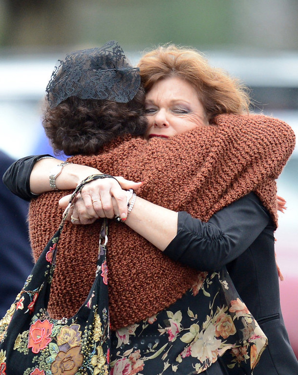 Description of . Veronika Pozner (Back to Camera) receives a hug as she leaves the funeral services of her six year-old son Noah Pozner, who was killed in the shooting massacre in Newtown, CT, at Abraham L. Green and Son Funeral Home on December 17, 2012 in Fairfield, Connecticut. Today is the first day of funerals for some of the twenty children and seven adults who were killed by 20-year-old Adam Lanza on December 14, 2012.  AFP PHOTO / Don EMMERT/AFP/Getty Images