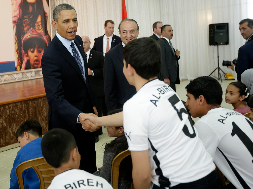 Description of . President Barack Obama greets members of a local youth soccer team during his visit to the Al-Bireh Youth Center in the West Bank city of Ramallah, Thursday, March 21, 2013. (AP Photo/Pablo Martinez Monsivais)